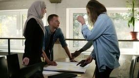 Grupo de personas multicultural - mujer musulmán, hombre africano y hombre y mujer caucásicos - discusión de un proyecto en ofici almacen de metraje de vídeo