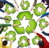 Grupo de personas multiétnico con el reciclaje de símbolo Fotos de archivo libres de regalías