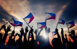Grupo de personas que agita banderas filipinas en Lit trasero fotografía de archivo libre de regalías
