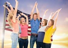 Grupo de personas que anima contra bandera americana Imagenes de archivo