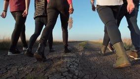 Grupo de personas que camina a lo largo del camino de tierra metrajes