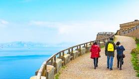 Grupo de personas que camina a lo largo de una trayectoria contra paisaje marino mediterráneo imagen de archivo