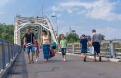 Grupo de personas que camina a través del puente peatonal Fotografía de archivo