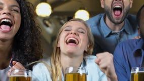 Grupo de personas que celebra la victoria preferida del equipo de deportes, cerveza que tintinea en pub almacen de metraje de vídeo