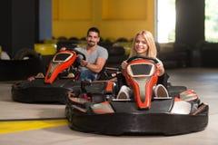 Grupo de personas que conduce la raza de Karting del kart imagenes de archivo