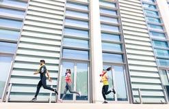 Grupo de personas que corre en área urbana moderna de la ciudad Imagenes de archivo