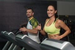 Grupo de personas que corre en las ruedas de ardilla en gimnasio fotografía de archivo