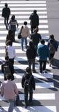 Grupo de personas que cruza la calle Imagen de archivo libre de regalías