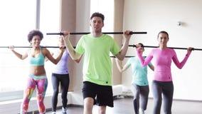 Grupo de personas que ejercita con las barras en gimnasio almacen de video