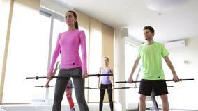 Grupo de personas que ejercita con las barras en gimnasio metrajes