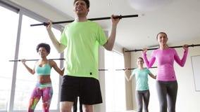 Grupo de personas que ejercita con las barras en gimnasio almacen de metraje de vídeo