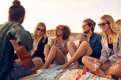Grupo de personas que escucha el amigo que toca la guitarra en la playa Foto de archivo