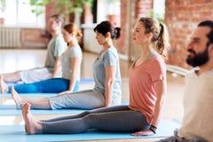 Grupo de personas que hace actitud del personal de la yoga en el estudio fotografía de archivo libre de regalías
