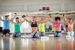 Grupo de personas que hace ejercicio con caucho resistente imagen de archivo libre de regalías