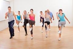 Grupo de personas que hace ejercicios de los aeróbicos Foto de archivo libre de regalías