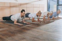 grupo de personas que hace el tablón en las esteras de la yoga fotos de archivo libres de regalías