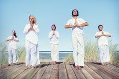 Grupo de personas que hace yoga en la playa Imagen de archivo