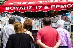 Grupo de personas que lee los periódicos en Atenas Grecia Imagen de archivo libre de regalías