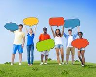 Grupo de personas que lleva a cabo burbujas coloridas del discurso Foto de archivo