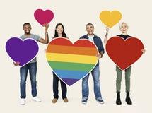 Grupo de personas que lleva a cabo corazones coloridos fotos de archivo libres de regalías