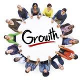 Grupo de personas que lleva a cabo las manos alrededor de crecimiento de la letra Imagen de archivo libre de regalías