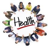 Grupo de personas que lleva a cabo las manos alrededor de salud de la letra Fotos de archivo libres de regalías