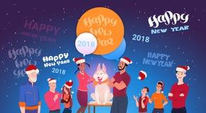 Grupo de personas que lleva a Santa Hats With Cute Dog sobre letras de la Feliz Año Nuevo en fondo azul Fotografía de archivo libre de regalías