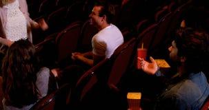 Grupo de personas que obra recíprocamente mientras que mira la película 4k almacen de metraje de vídeo