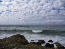 Grupo de personas que practica surf que esperan ondas imagen de archivo