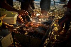 Grupo de personas que se ayuda a hacer la cena deliciosa antes de puesta del sol en la playa en Tailandia imagenes de archivo