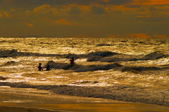Grupo de personas que se baña en el mar Báltico durante puesta del sol fotos de archivo
