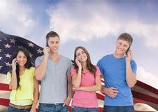 Grupo de personas que se opone a bandera americana y que habla en el teléfono móvil Foto de archivo libre de regalías