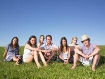 Grupo de personas que se sienta en la hierba Fotos de archivo libres de regalías