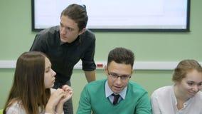 Grupo de personas que se sienta en la tabla, trabajando cuidadosamente con el ordenador portátil en sala de clase y participando  almacen de metraje de vídeo
