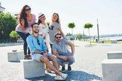 Grupo de personas que se sienta en los amigos multirraciales de una escalera al aire libre - que hablan y que se divierten en una Foto de archivo libre de regalías