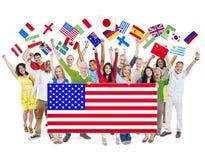 Grupo de personas que sostiene banderas nacionales Imagen de archivo libre de regalías