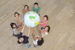 Grupo de personas que sostiene el globo de la tierra Fotos de archivo libres de regalías