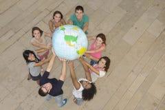 Grupo de personas que sostiene el globo de la tierra Foto de archivo
