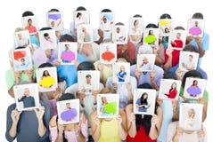 Grupo de personas que sostiene las tabletas delante de caras Imagen de archivo libre de regalías