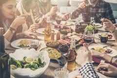 Grupo de personas que tiene cena de la unidad de la comida imagen de archivo