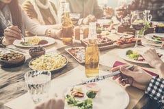 Grupo de personas que tiene cena de la unidad de la comida foto de archivo