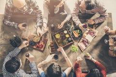 Grupo de personas que tiene cena de la unidad de la comida imagenes de archivo