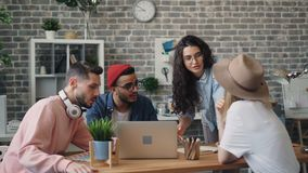 Grupo de personas que tiene conversación alrededor del ordenador portátil que discute ideas en oficina metrajes