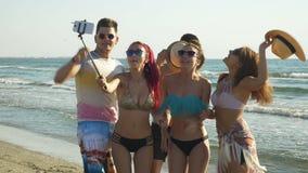 Grupo de personas que toma selfies y que tiene llamada video en la orilla de una playa hermosa almacen de metraje de vídeo