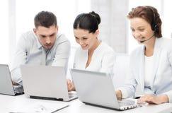 Grupo de personas que trabaja con los ordenadores portátiles en oficina imagen de archivo