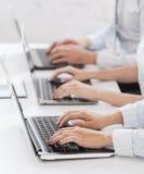 Grupo de personas que trabaja con los ordenadores portátiles en oficina foto de archivo libre de regalías