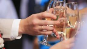 Grupo de personas que tuesta en una celebración que tintinea sus vidrios juntos en la enhorabuena, cierre encima de la vista de s almacen de video