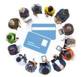 Grupo de personas que usa los dispositivos de Digitaces con símbolo de la tarjeta de crédito Foto de archivo