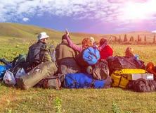 Grupo de personas y muchas mochilas en césped herboso Foto de archivo