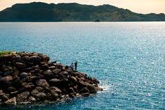 Grupo de pescadores que pescam no cais da rocha no por do sol com o mar azul calmo Foto de Stock Royalty Free